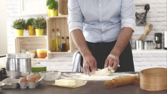 Man kneading dough, baking bread or pizza