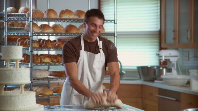 MS Man kneading dough in bakery looks up and smiles at camera / racks of bread in background