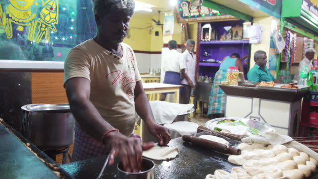 vidéos et rushes de man kneading flour to make dosa at india street food market - indien d'inde