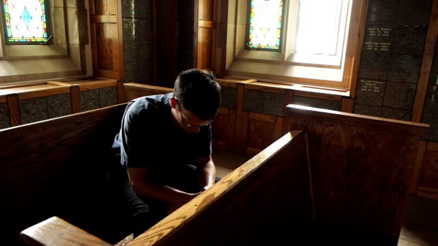 stockvideo's en b-roll-footage met man kneeling in prayer - kerk
