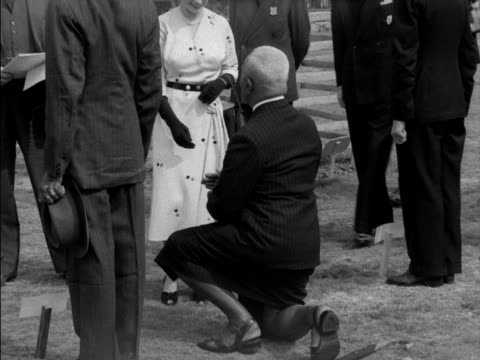 a man kneels as he shakes the queen's hand during a tree planting ceremony in windsor great park 1953 - イギリス バークシャー点の映像素材/bロール