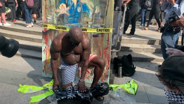 a man kneels on a black mannequin with writing i can't breathe in front of artwork writing enough is enough as people chant and clap as demonstrators... - i can't breathe stock videos & royalty-free footage