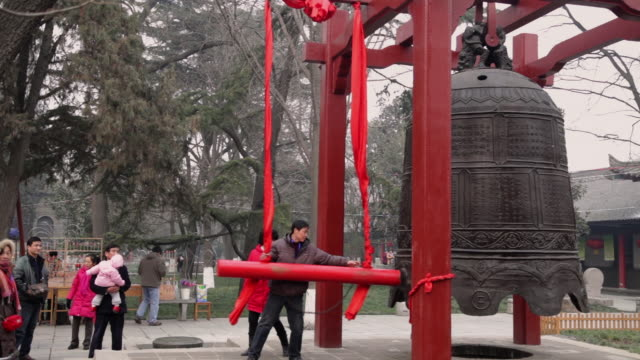 MS Man knocking bell to pray for good luck at temple fair to celebrate Chinese spring festival / xi'an, shaanxi, china