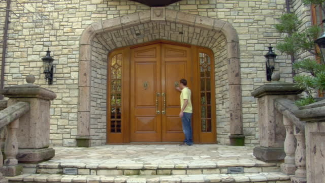 MS, Man knocking on door then entering mansion, Beverly Hills, California, USA
