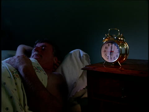 a man knocks his alarm clock off the bedside table. - alarm clock stock videos & royalty-free footage