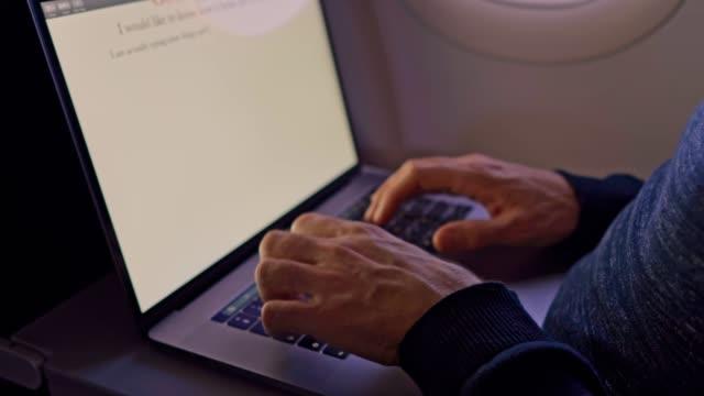 en man knackar på en bärbar dator i ett flyg plan på en flygning-närbild - human body part bildbanksvideor och videomaterial från bakom kulisserna