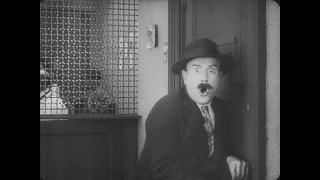 1917 man (fatty arbuckle) knocks on door of secret betting shop scaring customers into hasty exit because he is dressed as a policeman - 無声映画点の映像素材/bロール