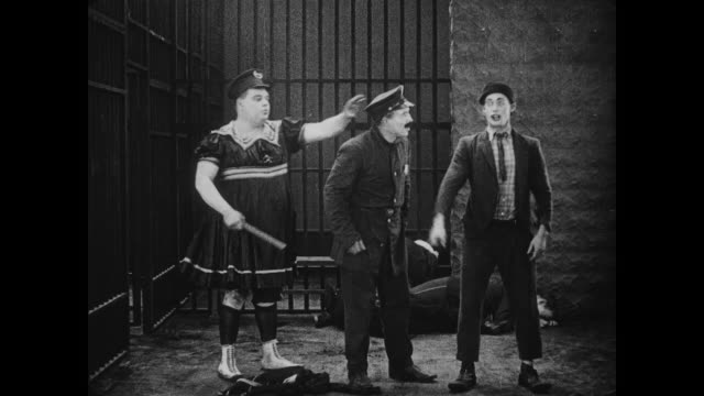 vídeos de stock e filmes b-roll de 1917 man (fatty arbuckle) knocks out police officer in jail cell - maça