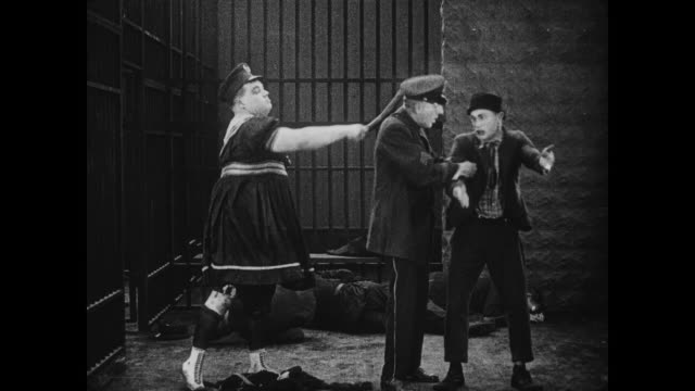 stockvideo's en b-roll-footage met 1917 man (fatty arbuckle) knocks out two more policemen in jail cell before attacking cellmate - 1917