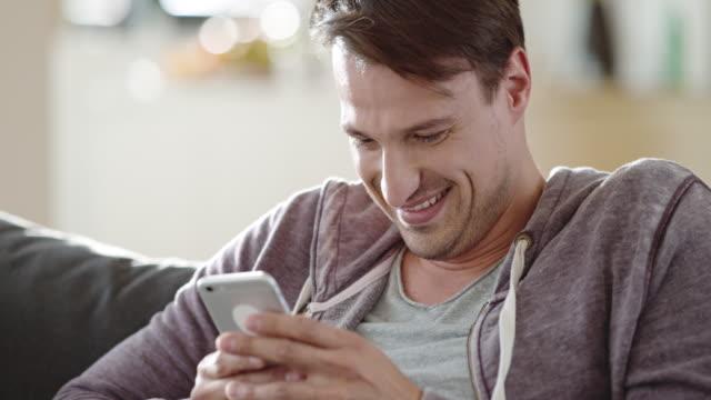 vidéos et rushes de homme en riant tout en sms sur le canapé - message sms