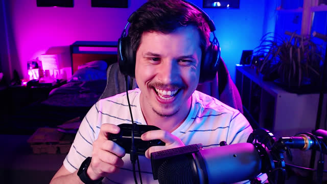 man laughs playing multiplayer video game with friends online on video call - headset stock videos & royalty-free footage