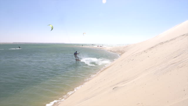 man launching of a sand dune for kiteboarding on a kite board near a beach. - 4k resolution stock videos & royalty-free footage