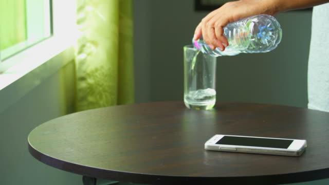 vídeos de stock, filmes e b-roll de homem lançar telefone inteligente e sirva-se de água - armação de janela