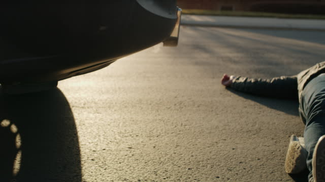 man laying in street with cell phone near car bumper after accident / cedar hills, utah, united states - bumper stock videos & royalty-free footage
