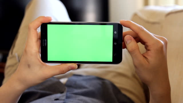 man laying on couch and using mobile phone with green screen in landscape mode
