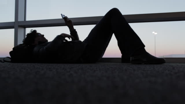 man laying on floor, looking at mobile phone at dusk in airport departure area. - boredom stock videos & royalty-free footage