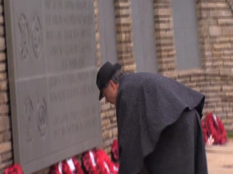 stockvideo's en b-roll-footage met a man lays a wreath on a memorial in remembrance of the victims of the falklands war - atlantische eilanden
