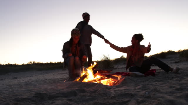 WS Man lays blanket on sand beside campfire then beckons his girlfriend to sit next to him, their friend pours coffee