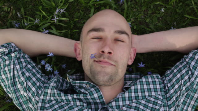 man lays on his back in grass and eats flower