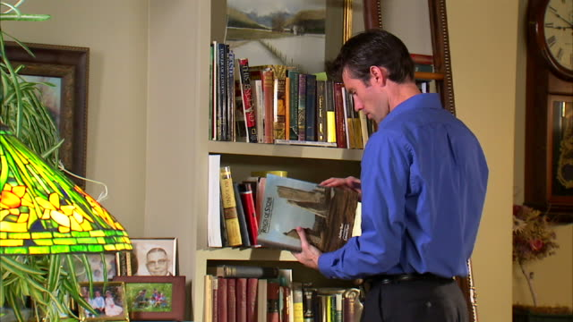 MS Man leafing through books at bookshelf in room / Salt Lake City, Utah, USA