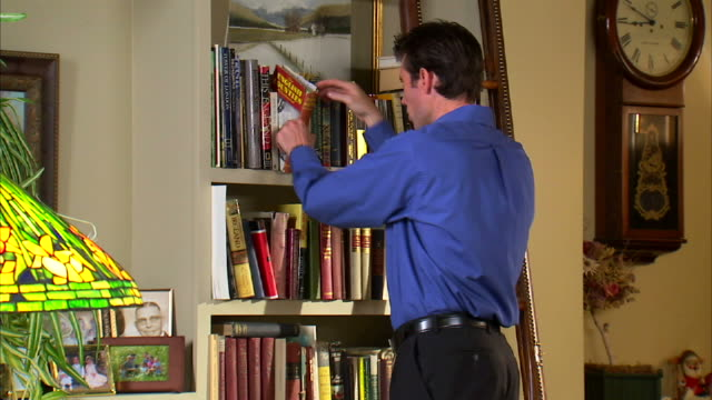 ms man leafing through books at bookshelf in room / salt lake city, utah, usa - hardcover book stock videos and b-roll footage