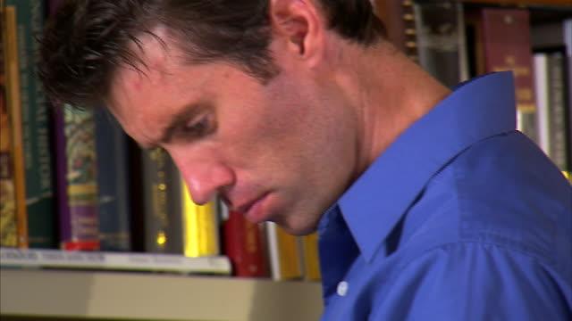 CU TU Man leafing through books at bookshelf / Salt Lake City, Utah, USA