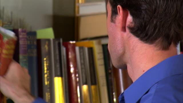 CU TD Man leafing through books at bookshelf / Salt Lake City, Utah, USA