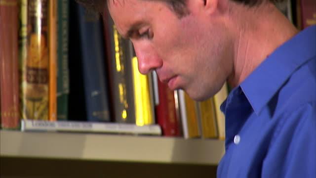 cu tu man leafing through books at bookshelf / salt lake city, utah, usa - hardcover book stock videos and b-roll footage