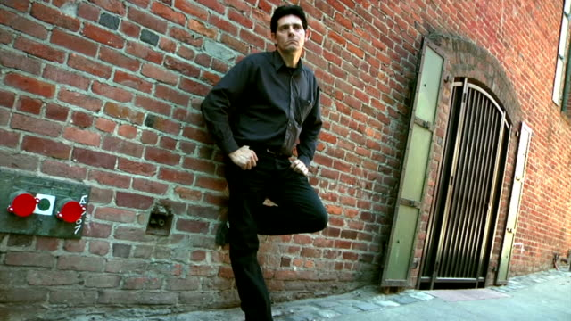 stockvideo's en b-roll-footage met man leaning against a brick wall - achterover leunen