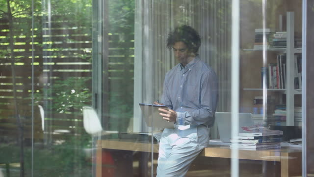 vídeos y material grabado en eventos de stock de ms ds r/f man leaning against desk in glass walled home office writing on notepad looking out window and walking out office - mirar por la ventana