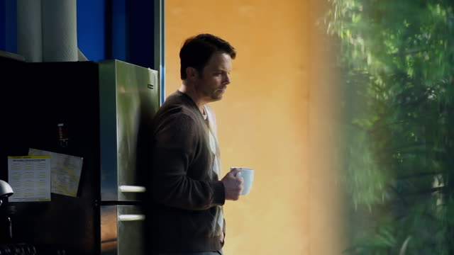 MS DS R/F man leaning against wall in home kitchen holding coffee cup looking out window