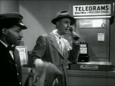 b/w 1956 man leaning against wall ordering telegram on phone / black porter wating in foreground - telegram stock videos and b-roll footage