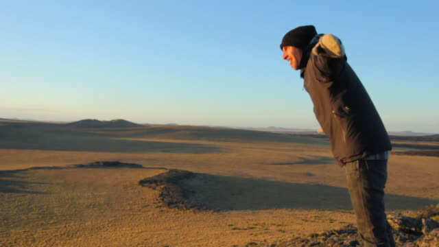 Man leaning in strong wind in vulcanic landscape in Patagonia