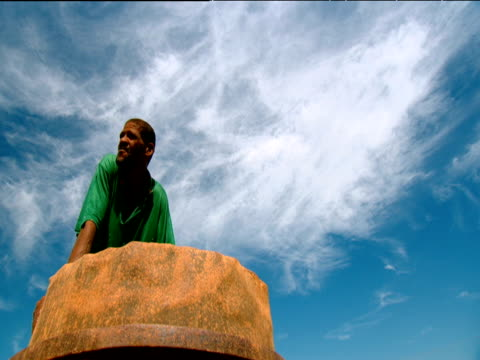 man leaning on barrel under blue sky with wispy clouds kimberley south africa - wispy stock videos and b-roll footage