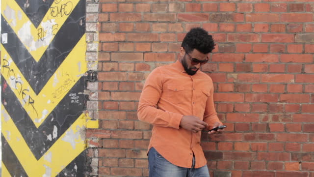Man leaning on brick wall, texting, taking off sunglasses and looking into camera smiling