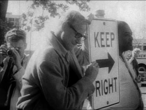 b/w 1963 man leaning on sign crying outdoors after john kennedy's assassination / newsreel - attentat auf john f. kennedy stock-videos und b-roll-filmmaterial