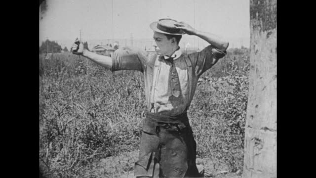 1922 man (buster keaton) leans against palm tree in open field - flexing muscles stock videos and b-roll footage