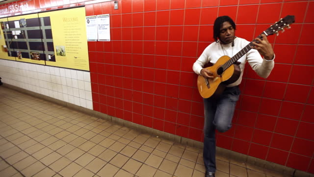 Man leans against wall playing acoustic guitar for tips in New York City subway