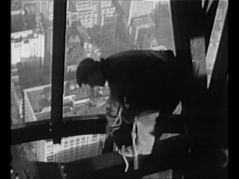 Man leans down off of beam outside the Empire State Building / man stands on beam pulls rope upwards / tiltdown shot window cleaners on scaffolding...