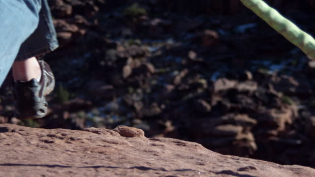 MS SLO MO Man leaping off cliff in desert / Moab, Utah, United States