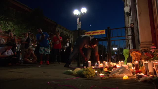 man leaves a candle at a makeshift memorial following a mass shooting in the oregon historic district of dayton, ohio. - dayton ohio stock videos & royalty-free footage
