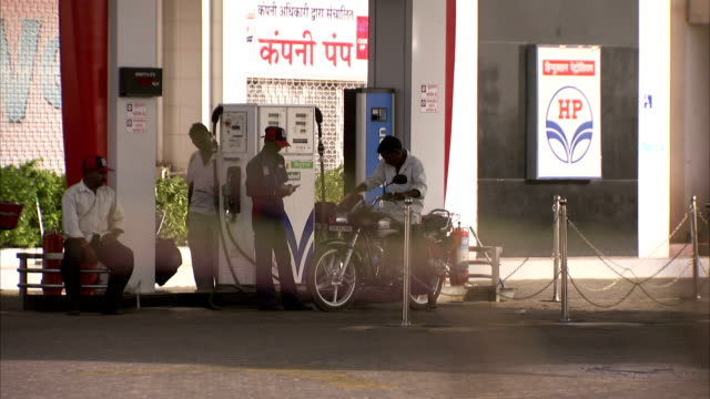 a man leaves a petrol station on a motorbike after refueling. - fuel pump stock videos and b-roll footage