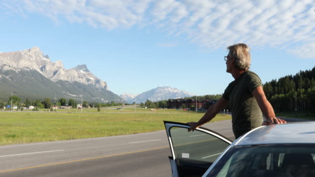 man leaves car door, looks down highway to mountain scene - only mature men stock videos & royalty-free footage
