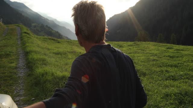 vídeos y material grabado en eventos de stock de man leaves car door, walks into meadow to look out to mountains - derecho