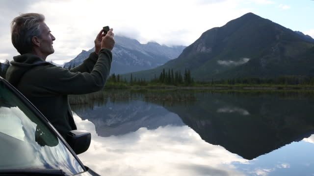 Man leaves car, takes smart phone pic of mountain lake