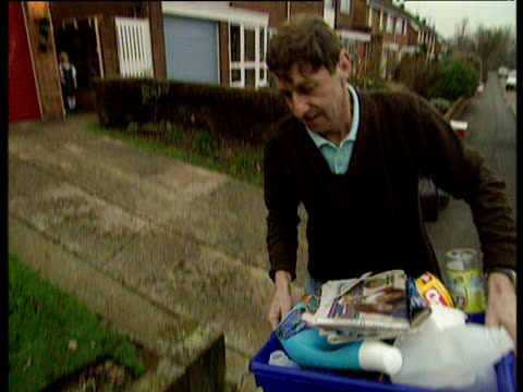 Man leaves house and puts blue recycling box on pavement for collection