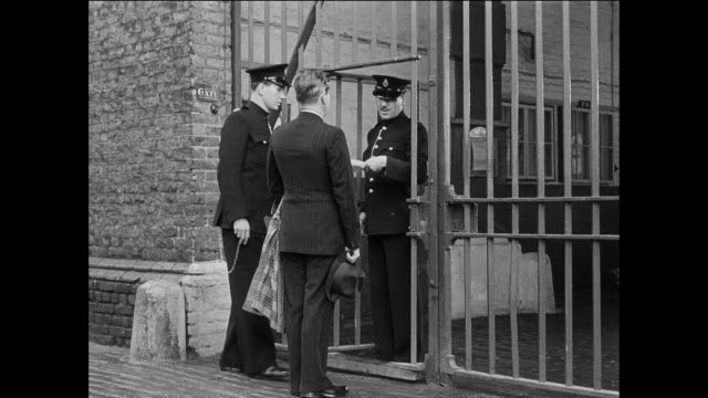 MONTAGE man leaves prison for the outside / UK / Guard walks man to gate / guard opens gate / guard hand guard document / man walks through gate / guard closes gate / guard opens door / man walks out door to woman / guard closes door
