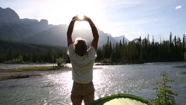 Man leaves tent to greet sunrise view over mountains, river