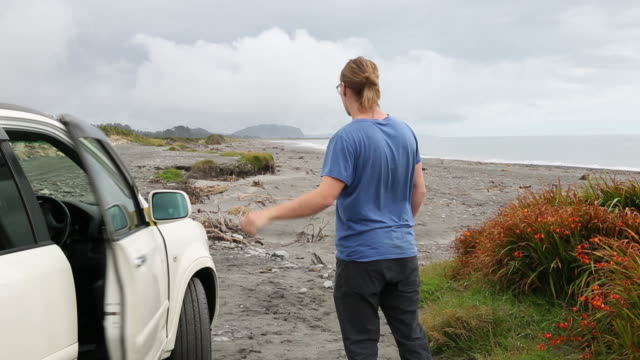 Man leaves vehicle on beach and looks out to sea