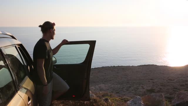 vídeos de stock e filmes b-roll de man leaves vehicle, walks out to viewpoint above sea - desembarcar